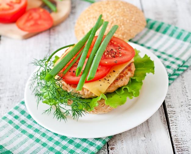 チキンバーガー、トマト、チーズ、レタスのサンドイッチ