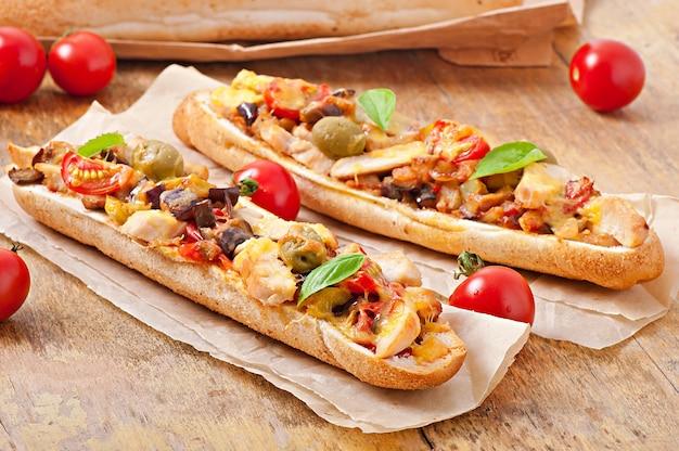Большой бутерброд с жареными овощами (цуккини, баклажаны, помидоры) и курицей с сыром и базиликом на старых деревянных фоне