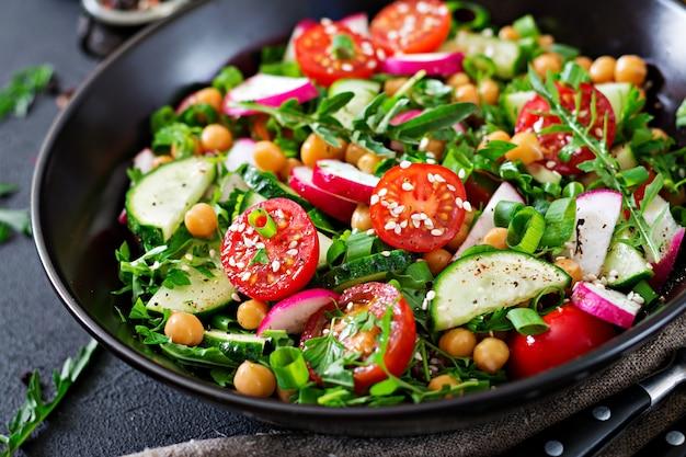 ひよこ豆、トマト、きゅうり、大根、緑のサラダ。ダイエット食品。ビーガンサラダ