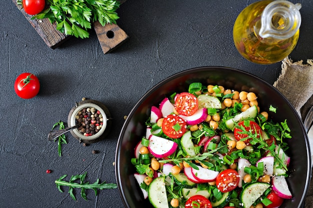 ひよこ豆、トマト、きゅうり、大根、緑のサラダ。ダイエット食品。ビーガンサラダ上面図。平置き