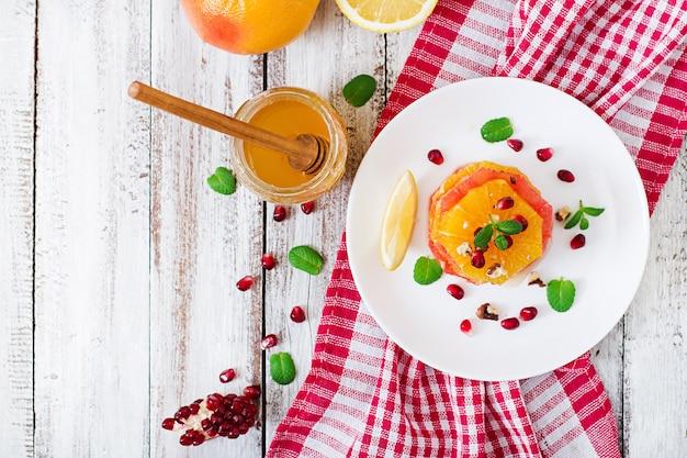 グレープフルーツとオレンジ、ザクロの種、蜂蜜とレモンのフルーツサラダ、ミントで飾られています。上面図