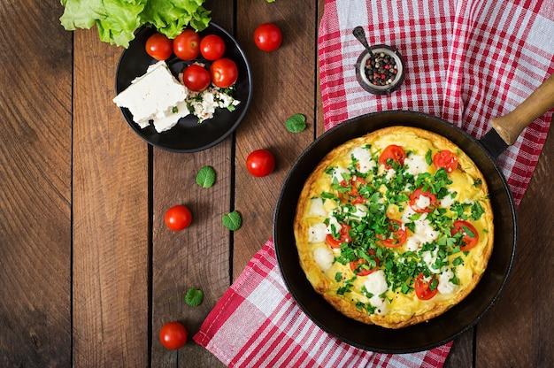 フライパンにトマト、パセリ、フェタチーズのオムレツ。上面図