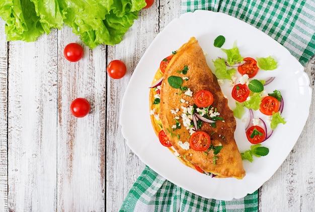 白い皿にトマト、パセリ、フェタチーズのオムレツ。上面図