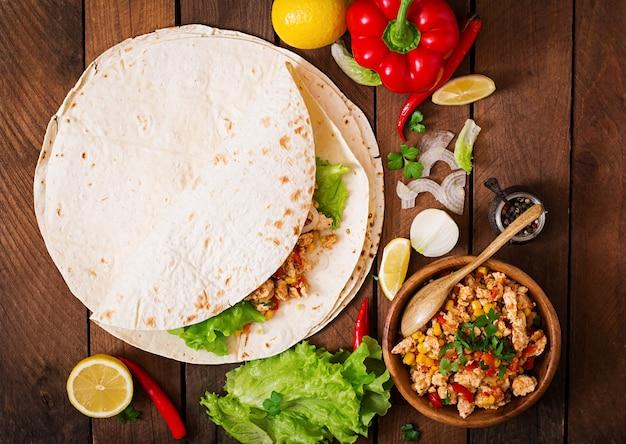 Ингредиенты для буррито обертывают куриное мясо, кукуруза, помидоры и перец на деревянный стол. вид сверху