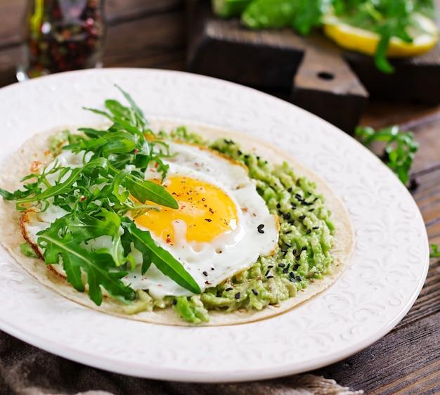 ワカモレ、目玉焼き、ルッコラのタコス。健康食品。便利な朝食。