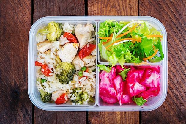 ランチボックスチキン、ブロッコリー、グリーンピース、トマトとご飯と赤キャベツ。健康食品。取り除く。弁当箱。上面図