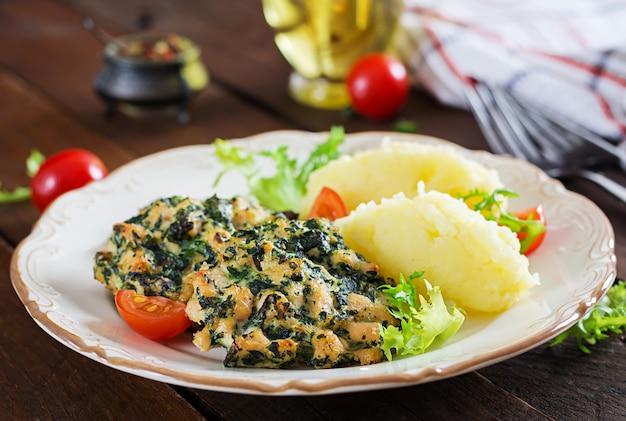 Запеченный стейк нарезанного куриного филе со шпинатом и гарниром из картофельного пюре. европейская кухня диетическое питание