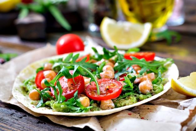 ワカモレ、ひよこ豆、トマト、ルッコラのビーガンタコス。健康食品。便利な朝食