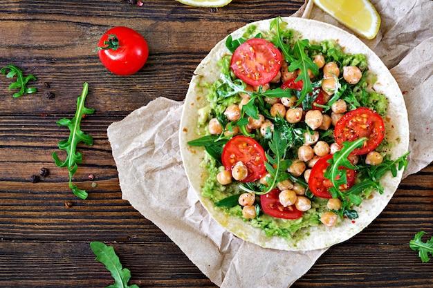 ワカモレ、ひよこ豆、トマト、ルッコラのビーガンタコス。健康食品。便利な朝食。平干し。上面図