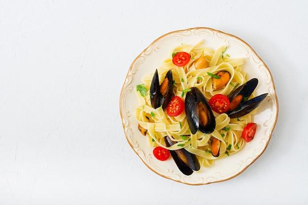 Паста феттучини из морепродуктов с мидиями на черном столе. средиземноморская деликатесная еда. квартира лежала. вид сверху
