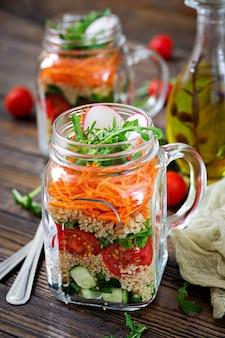 Салаты с киноа, руккола, редька, помидоры и огурцы в стеклянных банках на деревянный стол. здоровая пища, диета, детокс и вегетарианская концепция