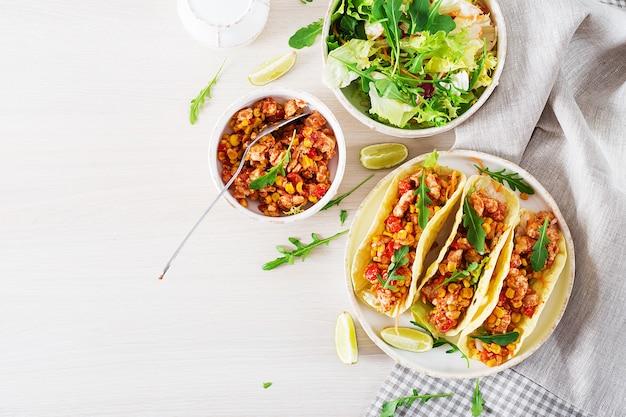 鶏肉、トウモロコシ、トマトソースのメキシコのタコス。ラテンアメリカ料理。タコス、トルティーヤ、ラップ。上面図。平置き