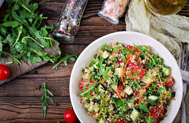 キノア、ルッコラ、大根、トマト、キュウリのボウルに木製のテーブルのサラダ。健康食品、ダイエット、デトックス、ベジタリアンのコンセプト。上面図。平置き
