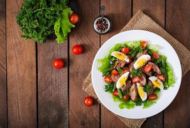 鶏レバー、インゲン、卵、トマト、バルサミコドレッシングの温かいサラダ。上面図