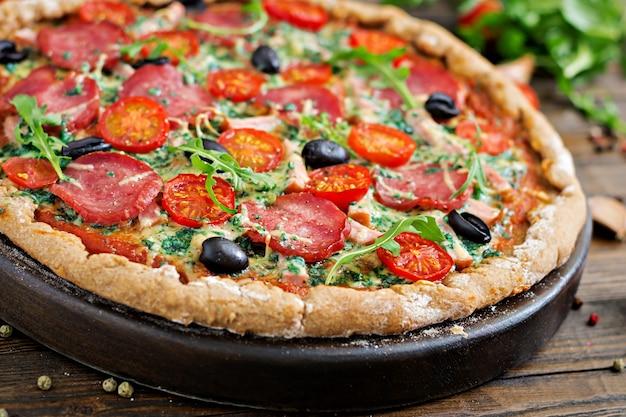 Пицца с салями, помидорами, оливками и сыром на тесте с цельной пшеничной мукой. итальянская еда.