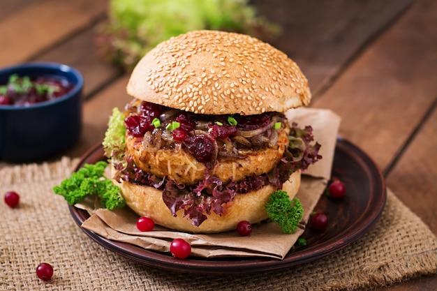 チーズ、カラメル玉ねぎ、クランベリーソースが付いたジューシーなターキーバーガーのハンバーガー