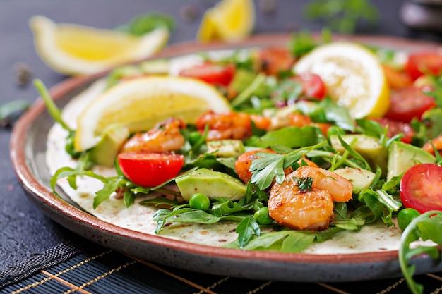 エビのトルティーヤタコスは、新鮮な野菜で顔を包みます。健康食品。メキシコ料理。