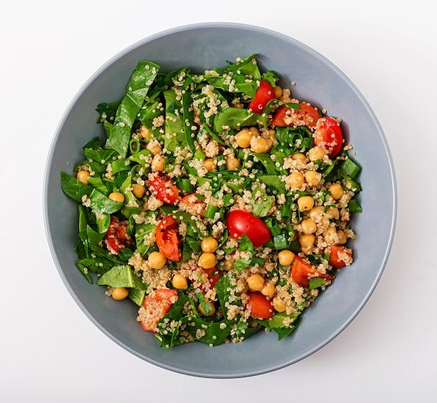 Диетическое меню. полезный веганский салат из свежих овощей - помидоров, нута, шпината и киноа в миске.