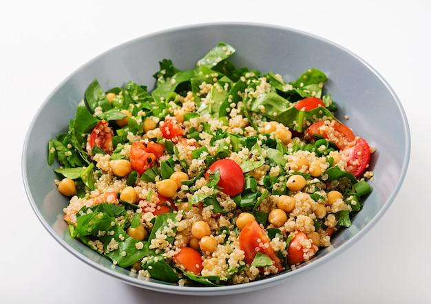 食事メニュー。新鮮な野菜のヘルシーなビーガンサラダ-トマト、ヒヨコ豆、ほうれん草、キノアをボウルに入れて。