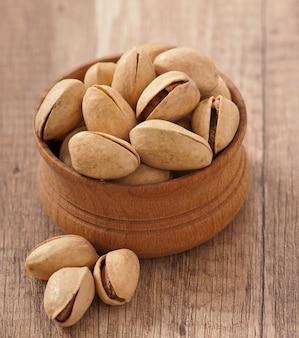 Треснутые и сушеные фисташковые орехи в деревянной миске