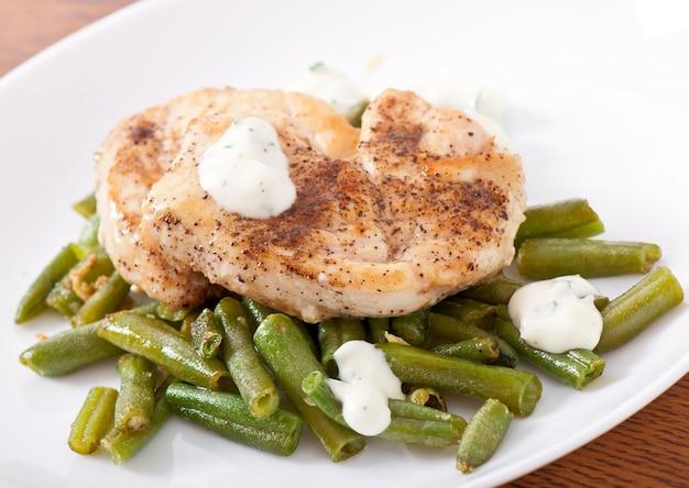 鶏胸肉のグリル、インゲンと白い皿にソース