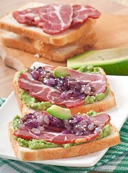 Бутерброд с ветчиной, соусом из авокадо и карамелизированным луком