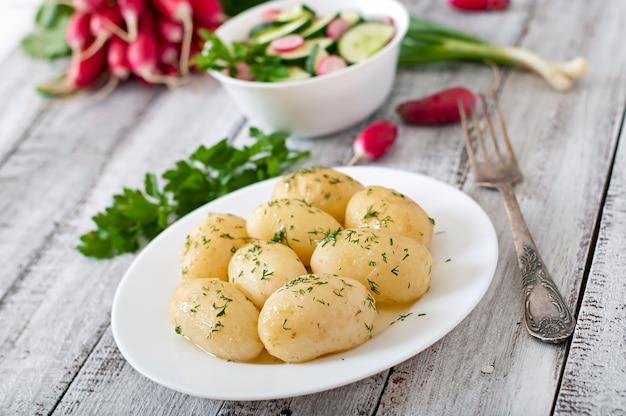 Молодой отварной картофель с маслом и укропом на белой тарелке