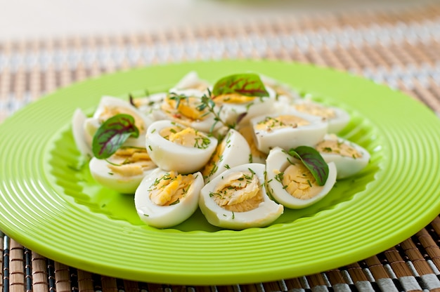 ゆでウズラの卵半分の緑のプレート