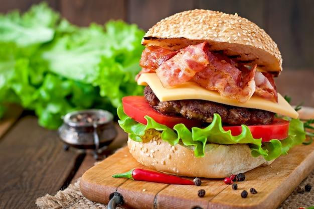 Большой бутерброд - гамбургер с говядиной, сыром, помидорами и жареным беконом