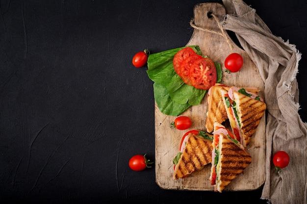 クラブサンドイッチパニーニ(ハム、トマト、チーズ、バジル)。フラットレイ。上面図