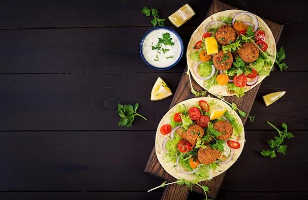 ファラフェルと新鮮なサラダのトルティーヤラップ。ビーガンタコスベジタリアンの健康食品。上面図