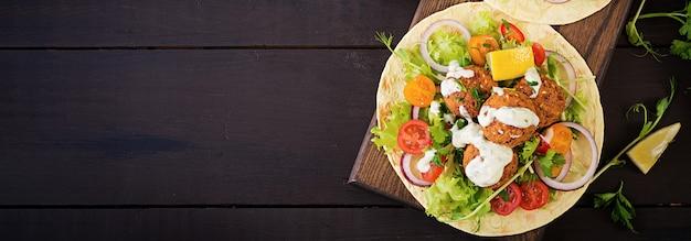 ファラフェルと新鮮なサラダのトルティーヤラップ。ビーガンタコスベジタリアンの健康食品。バナー。上面図