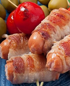 ベーコンのストリップにトマトとセージの葉を巻いたグリルソーセージ