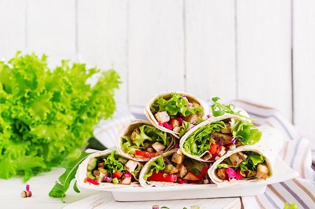 Куриный буррито. здоровый обед мексиканская уличная еда фахита тортилла обертывает с куриным филе на гриле и свежими овощами.
