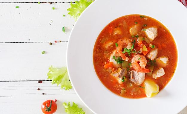 ブラジル料理:白い木製テーブルの上の皿にスパイシーなココナッツソースの魚とピーマンのモケカカピクサバ。ブラジルの魚のシチュー。上面図