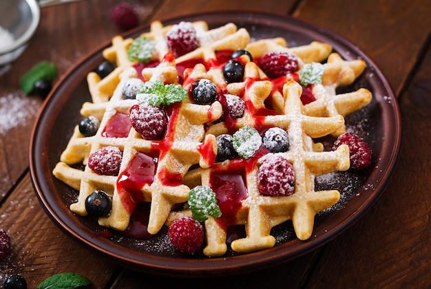 Бельгия вафли с малиной и сиропом на тарелку.