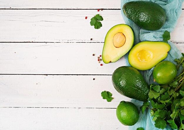 Спелый авокадо, лайм и кинза на деревянном столе. концепция здорового питания. вид сверху