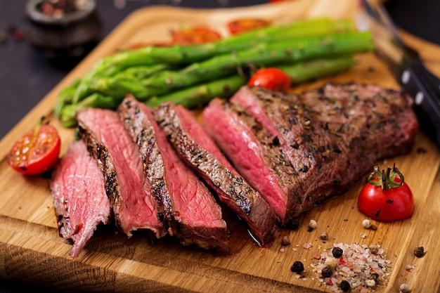 Сочный стейк редкой говядины со специями на деревянной доске и гарниром из спаржи.