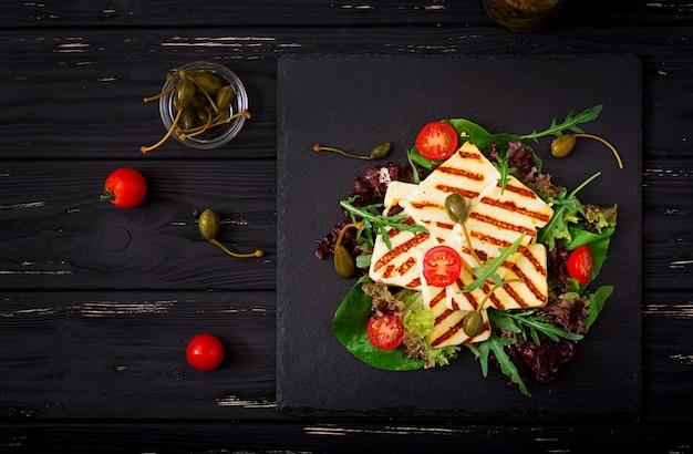 Свежий салат с жареным сыром, помидорами, каперсами, листьями салата и рукколой. квартира лежала. вид сверху