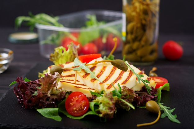Свежий салат с жареным сыром, помидорами, каперсами, листьями салата и рукколой.