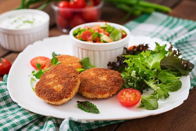 Маленькая куриная котлета с овощами на тарелке