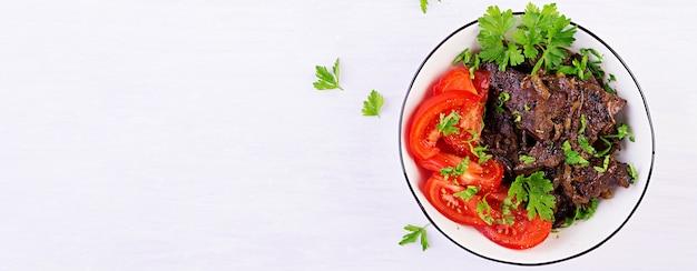 Жареная или жареная говяжья печень с луком и салатом из помидоров. ближневосточная кухня. баннер. вид сверху