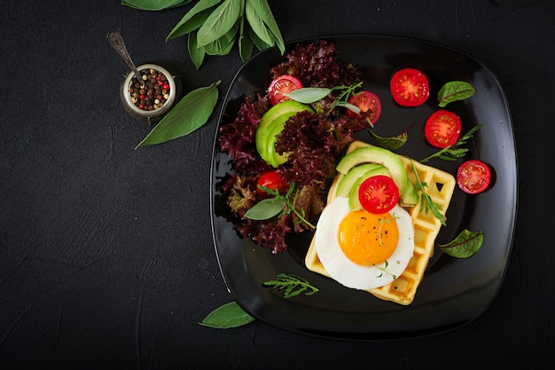 Здоровый завтрак - вафли, яйца, авокадо, помидоры и зелень. квартира лежала. вид сверху