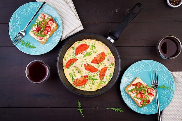 トマト、ハム、ネギ、暗いテーブルの上のイチゴのサンドイッチとオムレツ。フリッタータ-イタリアのオムレツ。上面図