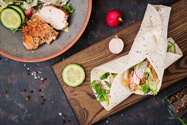 焼き鶏の胸肉、キュウリ、大根、レタスと健康的なメキシコのタコス。平干し。上面図