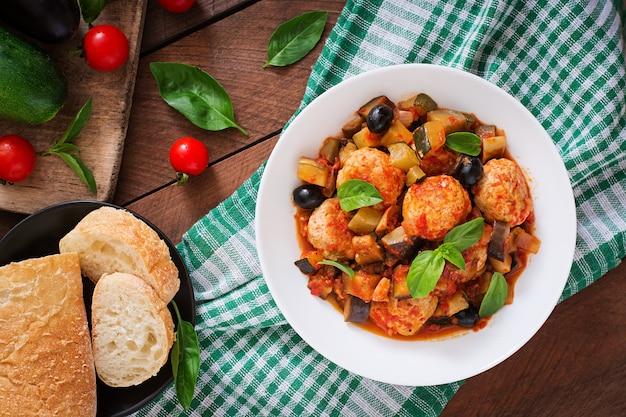 Сочные фрикадельки из мяса индейки с овощами (цуккини, баклажаны, оливки, помидоры). вид сверху
