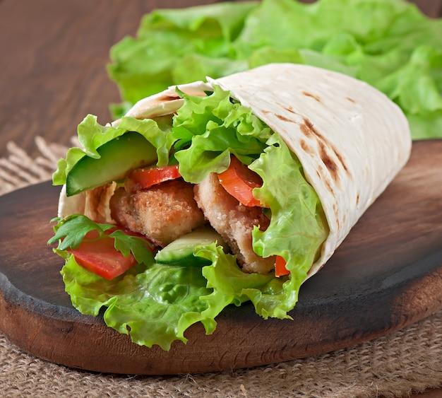 新鮮なトルティーヤをチキンナゲットと野菜のプレートで包みます