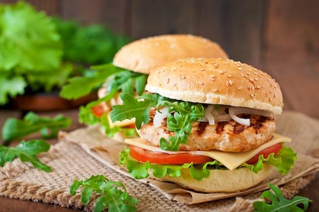 Бутерброд с куриным бургером, помидорами, сыром и салатом