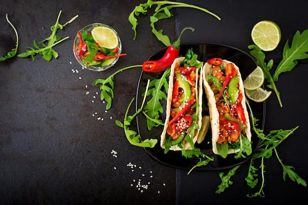 鶏ムネ肉のトマトソースとパプリカとルッコラのサルサを添えたメキシコのタコス。平干し。上面図