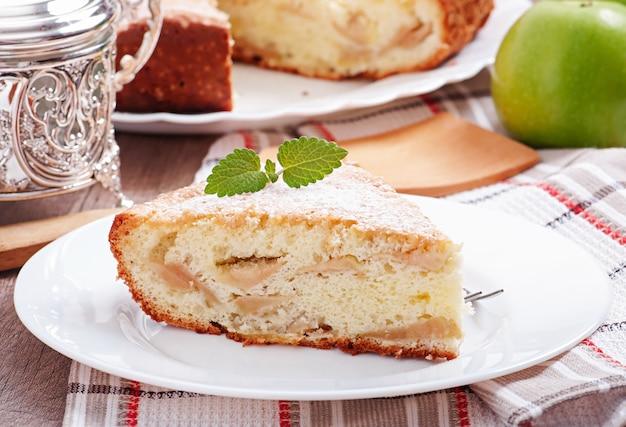 ミントの葉で飾られたプレート上のアップルフルーツのパイのスライス